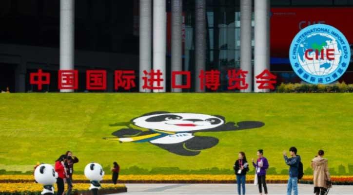首届中国国际进口博览会志愿者来到场馆内合影